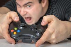 Homem viciado emocional que joga jogos de vídeo imagem de stock