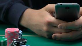 Homem viciado que joga o casino em linha, esporte que aposta, microplaquetas que encontram-se em torno do jogador video estoque