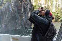 Homem vietnamiano que toma a foto que olha acima no navio de cruzeiros de Milford Sound foto de stock royalty free