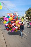 Homem vietnmese novo que vende balões coloridos na rua durante n imagem de stock