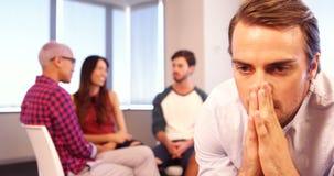 Homem virado que senta-se na cadeira com os colegas que discutem no fundo