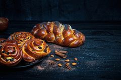 Close up photo of homemade buns and fresh cinnamon with cinnamon, almonds, star anise on dark rustik background. stock images