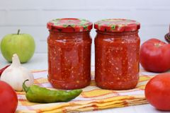 Homemade adzhika with apples in jars on a white background royalty free stock photo