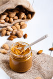 Homemade almond butter. Homemade almond butter in a glass jar and a jute bag and napkin Stock Image