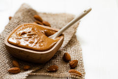 Homemade almond butter. Homemade almond butter in a wooden bowl and a bag of jute Royalty Free Stock Photography