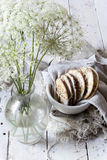 Homemade alternative cookies on bowl on white wooden table with wildflowers on vase Stock Image