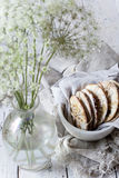Homemade alternative cookies on bowl on white wooden table with wildflowers on vase Stock Photo