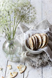 Homemade alternative cookies on bowl on white wooden table with wildflowers on vase Stock Photography