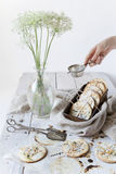 Homemade alternative cookies on vintage box on white wooden table with wildflowers on vase Stock Photo
