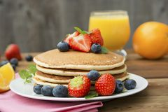 Homemade american pancake with fresh blueberries, strawberries and orange juice. Wooden rustic background. Homemade american pancake with fresh blueberries royalty free stock photography