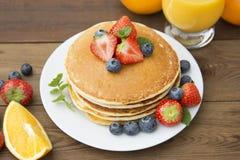 Homemade american pancake with fresh blueberries, strawberries and orange juice. Wooden rustic background. Homemade american pancake with fresh blueberries stock photo