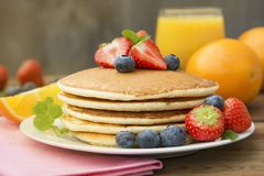 Homemade american pancake with fresh blueberries, strawberries and orange juice. Wooden rustic background. Homemade american pancake with fresh blueberries stock photos