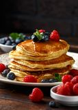 Homemade american pancakes with fresh blueberry, raspberries and honey. Healthy morning breakfast. rustic style stock photo