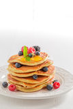 Homemade american pancakes with maple syrup and berries. Closeup of homemade american pancakes with maple syrup and berries royalty free stock image