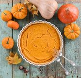 Homemade American pumpkin pie in white ceramic dish surrounded w Royalty Free Stock Image
