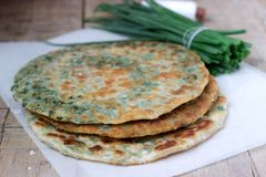 Homemade appetizing scallion pancakes and a bunch of green onions. Rustic style. royalty free stock photos
