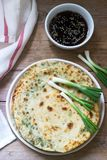 Homemade appetizing scallion pancakes and a bunch of green onions. Rustic style. stock photos