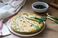 Homemade appetizing scallion pancakes and a bunch of green onions. Rustic style stock photos