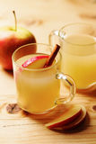 Homemade Apple Cider. In a glass cup with cinnamon and an apple slice on wooden table Royalty Free Stock Image