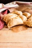 Homemade apple and cinnamon hand pies with cheddar cheese and sugar on top on a kitchen towel on a wooden board. Selective focus Royalty Free Stock Photography