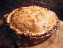 Homemade apple pie. On wooden board by brick wall Stock Image