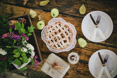 Homemade apple pie, apples and autumn leaves on the wooden table Stock Images