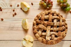 A homemade apple pie decorated with fresh apples, grapes and brown raisins on light wooden background with free copy space. On the left side. Top view Royalty Free Stock Photo