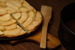 Homemade apple pie, and piece of pie with apple slices on cook board. Baking shovel and baking tray lying near pie Stock Photography