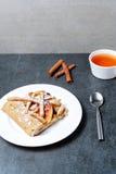 Homemade apple pie and tea and cinnamone sticks on dark background. Stock Photos