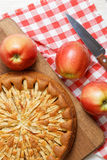 Homemade apple pie on white table. Homemade apple pie topped with slices of apples and cinnamon on wooden cutting board. Nearby are red apples, knife and stock image