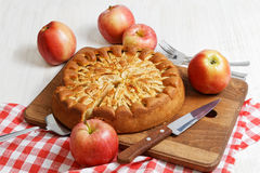 Homemade apple pie on white table. Homemade apple pie topped with slices of apples and cinnamon on white wooden table. Nearby are five red apples and knife on stock photo