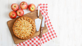 Homemade apple pie on white table. Homemade apple pie topped with slices of apples and cinnamon on white wooden table. Nearby are five red apples, knife stock image
