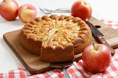 Homemade apple pie on white table. Homemade apple pie topped with slices of apples and cinnamon on white wooden table. Nearby are red apples and knife on stock images