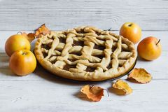 Homemade Apple pie on white wooden background, autumn mood, leaves and apples.  stock photos