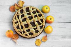Homemade Apple pie on white wooden background, autumn mood, leaves and apples royalty free stock photos