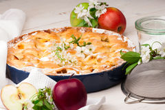 Homemade apple pie on a white wooden background. Homemade delicious fresh apple pie with aromatic spices, spring flowers and fresh apples on a white wooden stock photo