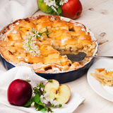 Homemade apple pie on a white wooden background. Homemade delicious fresh apple pie with aromatic spices, spring flowers and fresh apples on a white wooden stock image