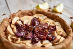 A homemade apple plums pie decorated with fresh apples, brown raisins and sesame on light wooden background. Close up view Stock Photos