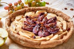 A homemade apple plums pie decorated with fresh apples, grapes, brown raisins and sesame on light wooden background. Close up view Royalty Free Stock Photos