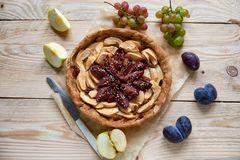 A homemade apple plums pie decorated with fresh grapes, plums, brown raisins, sesame and silver vintage knife on the wooden table. A homemade apple plums pie Royalty Free Stock Image