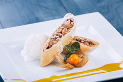 Homemade apple strudel with fresh apples, nuts and powdered sugar on a blue vintage wooden background. Apple strudel royalty free stock photos