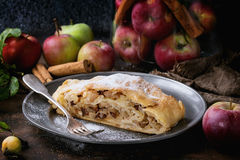 Homemade apple strudel. Sliced homemade apple strudel served with fresh apples in glass jar, cinnamon sticks and sugar powder on vintage metal plate with fork Stock Images