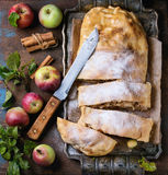 Homemade apple strudel. Sliced homemade apple strudel served with fresh apples with leaves, cinnamon sticks and sugar powder on vintage metal tray with knife Royalty Free Stock Photo
