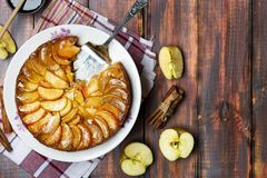 Apple tart with caramel and cinnamon on wooden table. Homemade apple tart with caramel and cinnamon on wooden table royalty free stock image