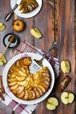 Apple tart with caramel and cinnamon on wooden table. Homemade apple tart with caramel and cinnamon on wooden table stock image