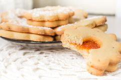 Homemade apricot jam Linzer bite with icing sugar on the white table close up Royalty Free Stock Photos