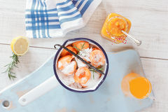 Homemade apricot marmalade. High angle view of sugared apricots in a pan, preserving jar and apricot juice, rustic style, on a wooden surface. Natural light stock photography