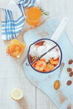Homemade apricot marmalade. High angle view of sugared apricots in a pan, preserving jar and apricot juice, rustic style, on a wooden surface. Natural light royalty free stock image