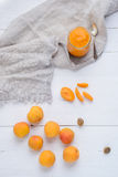 Homemade apricot puree in glass jar. Homemade apricot puree of fresh apricots in glass jar, teaspoon, apricot seeds and napkin on white wooden table royalty free stock photo