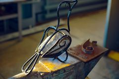 Homemade artificial bird of wire and stone body sitting on an anvil.  royalty free stock photography
